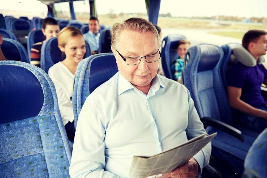 Man liest Zeitung während einer langen Busfahrt