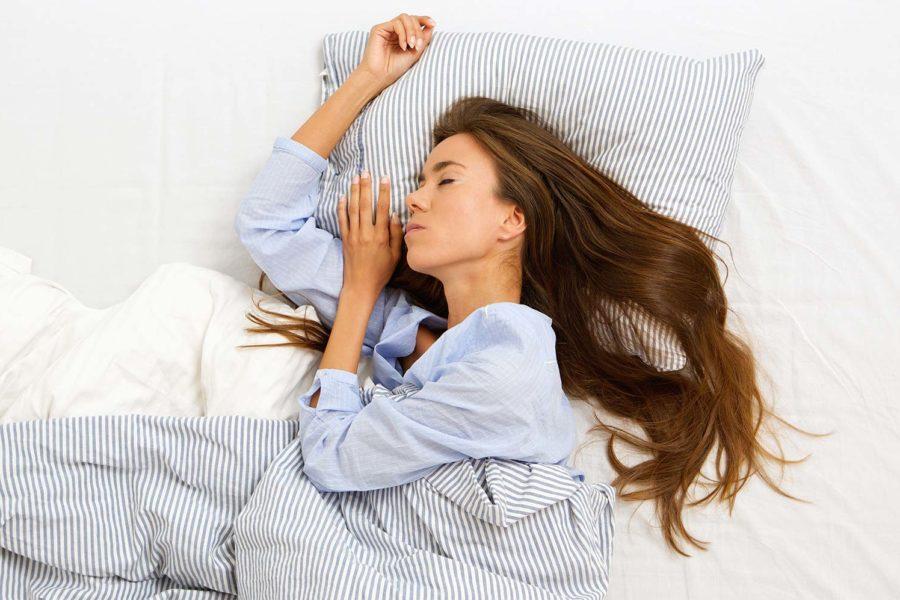 Eine junge Frau schläft in ihrem Bett