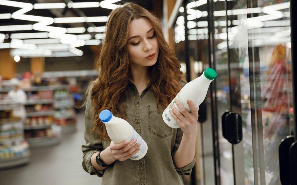 Eine Frau im Supermarkt betrachtet 2 Milchflaschen, die sind in den Händen hält
