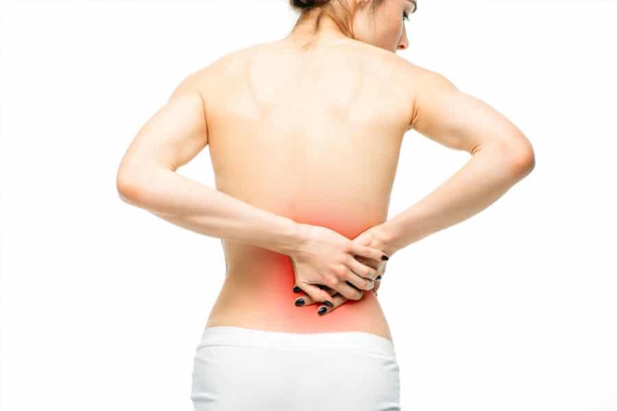 Frau greift sich an den Nierenbereich im Rücken, weil sie Schmerzen hat