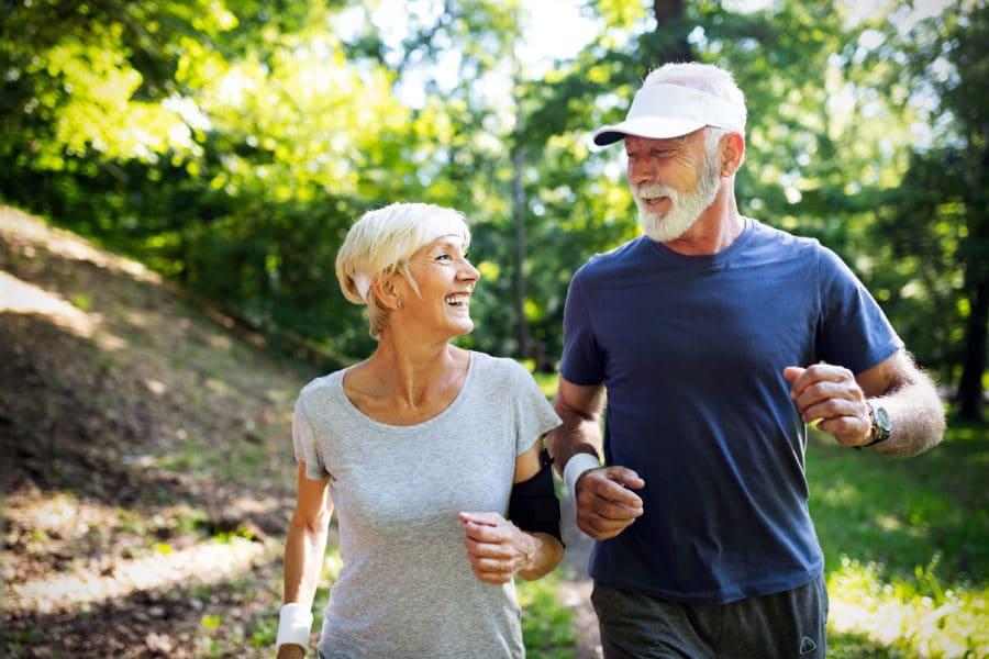 Ein älterer Mann und eine ältere Frau joggen im Wald