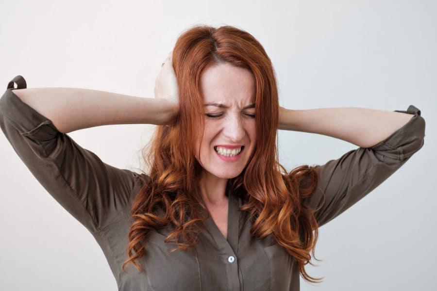 Frau mit schmerzvollem Gesichtsausdruck greif sich mit beiden Händen an die Ohren