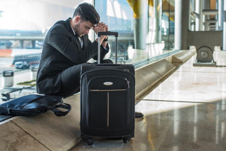 Den Jetlag bewältigen: Junger Mann im Businessanzug sitzt am Flughafen neben seinem Koffer und kann nicht schlafen