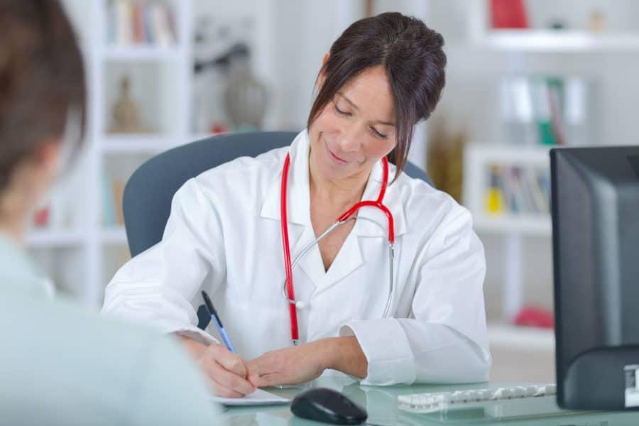 Für Gesundheit vorsorgen: Ärztin spricht in der Praxis mit einer Patientin