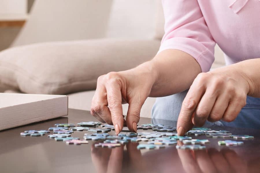 Ältere Frau stellt ein Puzzle zusammen