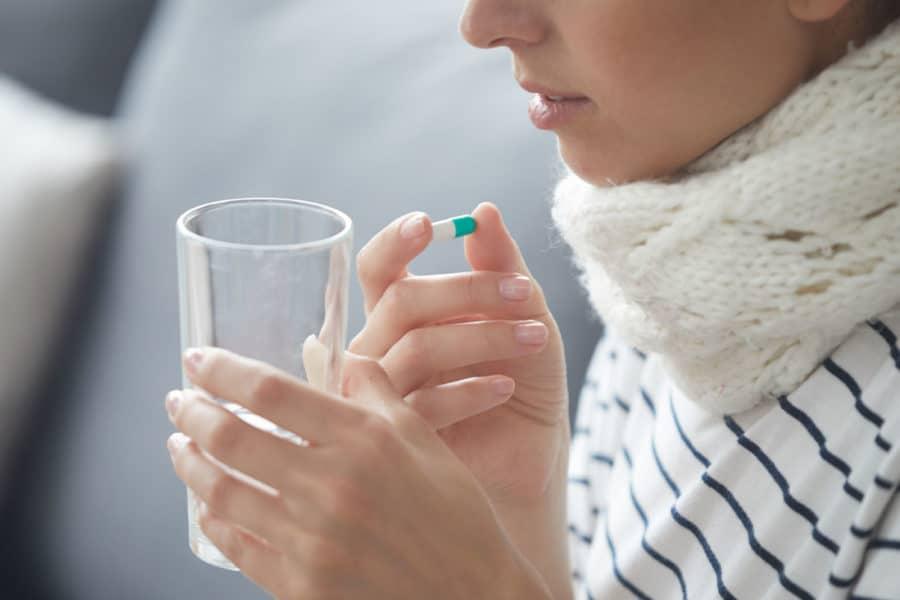 Eine Frau, die an einer Erkältung leidet, ist gerade dabei eine tablette mit einem Glas Wasser einzunehmen