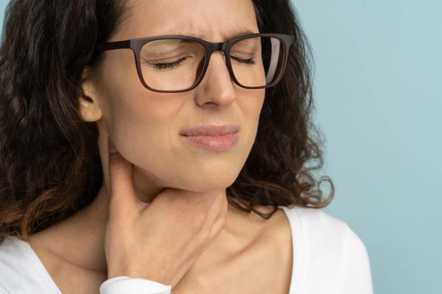 Eine junge Frau verzieht schmerzvoll das Gesicht und greift sich mit Ihrer Hand an ihren Hals