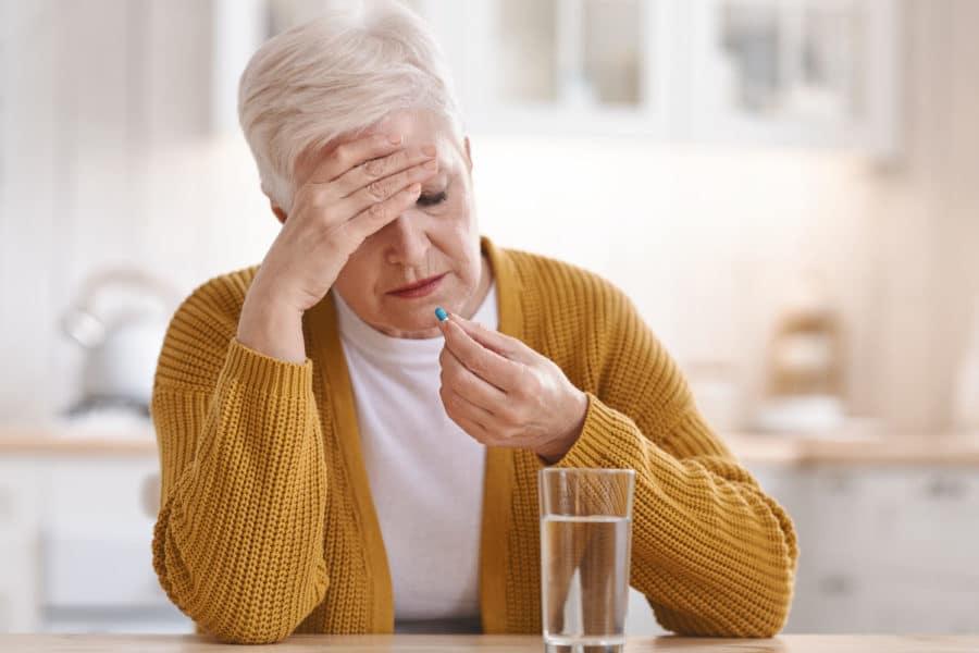 Ältere Frau greift nach einer Tablette