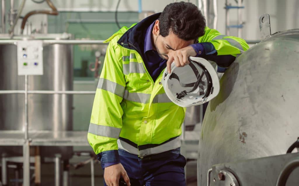 Erschöpfter Arbeiter in einer Fabrik lehnt sich an eine Maschine